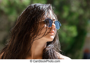 woman with wet hair wearing sunglasses - Portrait of...