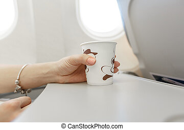 Woman drinking coffee on airplane. Female traveler seated in...