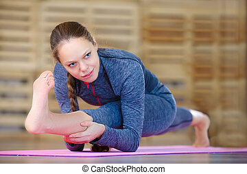 Woman doing yoga exercise called Revolved Head-to-Knee Pose...