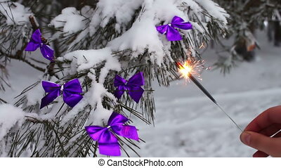 Decorated snowy forest tree with lilac ribbons and Bengal fire in a female hand