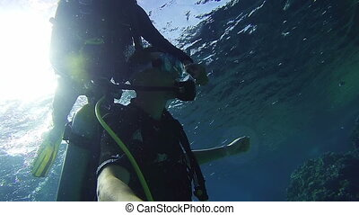 Underwater Scuba Diving Tourists with an Instructor in Red...