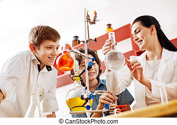 Cheerful attractive teacher showing a chemical flask
