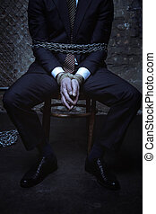 Business executive being captured in dark room - Punishment...