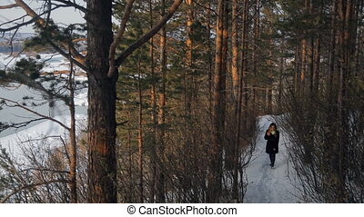 Young woman walking in wintertime pine forest outdoor. Happy...