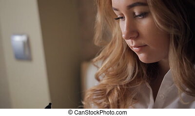 Young blonde woman writes in black ink, and looks away.