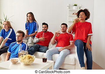 friends or football fans watching soccer at home -...