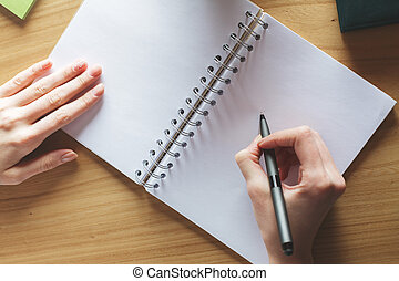 Girl writing in notepad with copyspace - Top view of white...