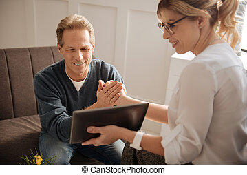 Happy delighted man looking at the tablet screen