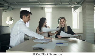 In the office three staff smile and collect documents after...