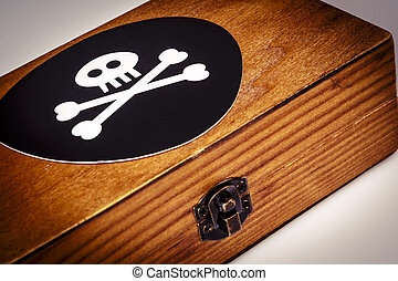 old wooden box with pirate symbol - skull and bones on black...