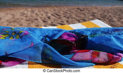 Sunglasses lying on a sun lounger in pareo on the background...