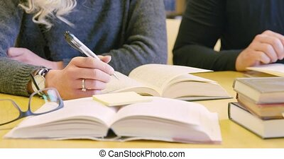 Close-up of two students team working in school library -...