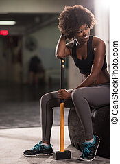 black woman after workout with hammer