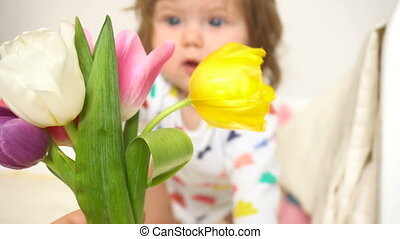 Little baby girl with bouquet of tulips