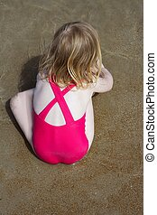 blond little girl swimsuit back playing on beach sand -...