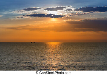 Seacoast skyline with beautiful sunset over small ship in the ocean