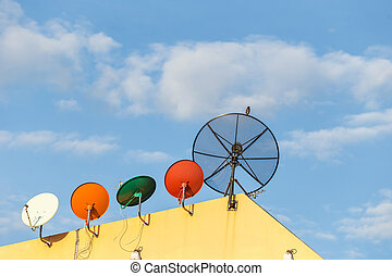 Several satellite dish installed on the house roof with blue...