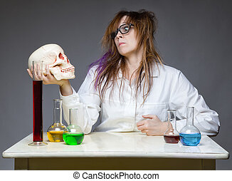 Serious scientist with human skull on gray background