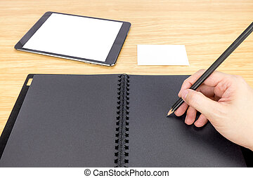 hand holding pencil writing on blank black book with table and business card on wooden table, Mock up for adding your content