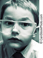 The boy scientist in the laboratory of protective glasses