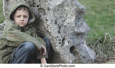 sad little boy outdoors at the day time