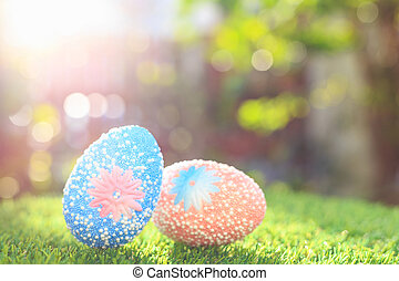 Color eggs on green grass with blur bokeh and sunlight...