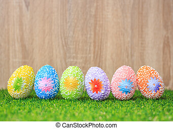 Color eggs on green grass with wooden wall background. For...