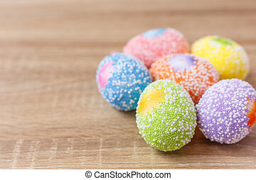 Artificial color eggs on wooden plank background. For Easter...