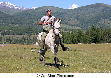 on horseback across the steppe - Asian boy very quickly goes...