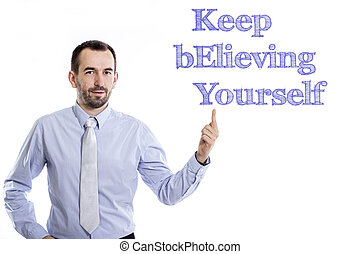 Keep Believing Yourself KEY - Young businessman with small beard pointing up in blue shirt