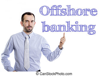 Offshore banking - Young businessman with small beard pointing up in blue shirt