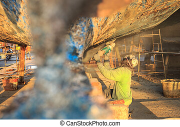 A man using grinder in preparation for anti foul paint being...