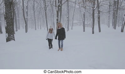 happy young couple run in winter forest