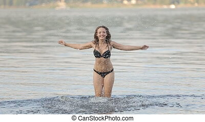 Cheerful girl splashing water towards the camera.