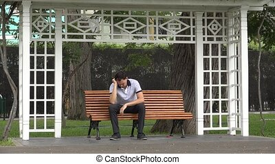 Sad Depressed Man Sitting On Park Bench