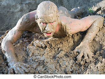 naked man mud - A naked man crawling through the mud