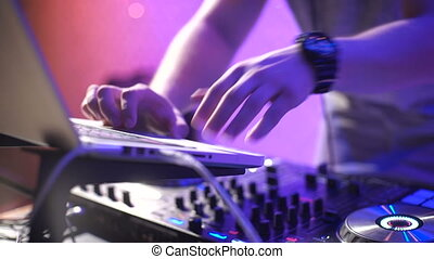 In the frame the DJ's hands in a nightclub. The party is in full swing and the fashionable disc jockey puts modern tracks and songs for the public.