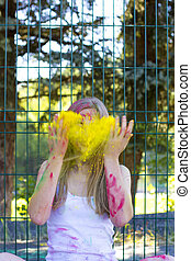 Young blonde woman throwing up yellow powder Holi in the...