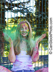 Young blonde woman tossing up green powder Holi in the park