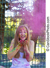 Young blonde model tossing up pink powder Holi in the park -...