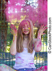 Happy blonde woman tossing up pink powder Holi in the park -...