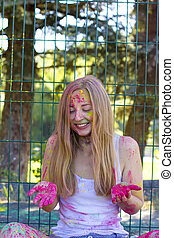 Happy young woman throwing up pink powder Holi in the park -...
