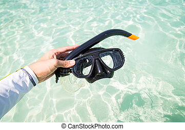 Hand holding snorkel goggles against beach and sea surface