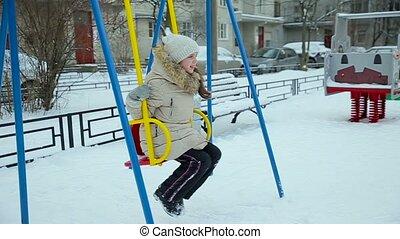 Little girl swinging on a swing slow motion
