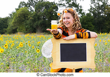 Bee - A woman dressed as a bee leaning against a sign and...