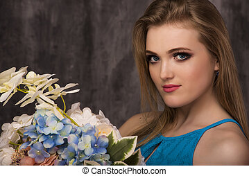 Beautiful happy young woman with flowers on grey background