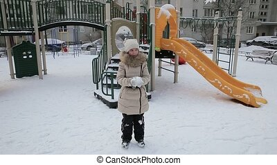 Small girl playing in the snow.