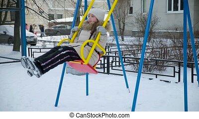 Little girl swinging on a swing