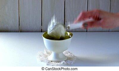 Female hand puts ice cream in ceramic vase