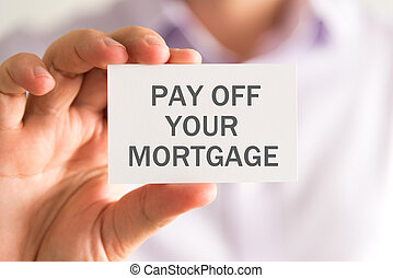 Businessman holding a card with PAY OFF YOUR MORTGAGE...